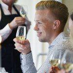 Ost och vinprovning i stockholm med en ung glad man som provar vitt vin