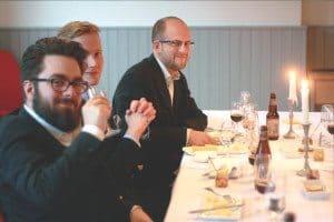 Ölprovning med glada deltagare och tänd ljus