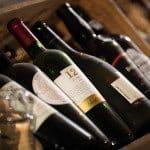 Olika röda viner i en trälåda förbereda inför en vinprovning