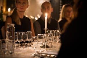 Några gäster på en mat- och dryckesaktivitet i Stockholm sitter i en mysig vinkällare längs ett fint uppdukat långbord med levande ljus och mysig stämning.