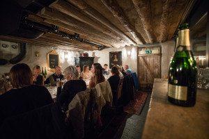 Företagsevent i Örebro i en vinkällare uppdukat med långbord. Glada människor sitter längs bordet och provar vin.