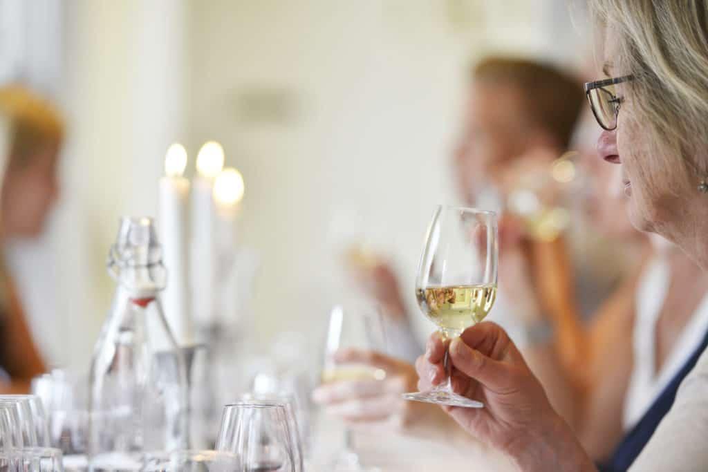 Vinprovning med några glada deltagare som provar vitt vin
