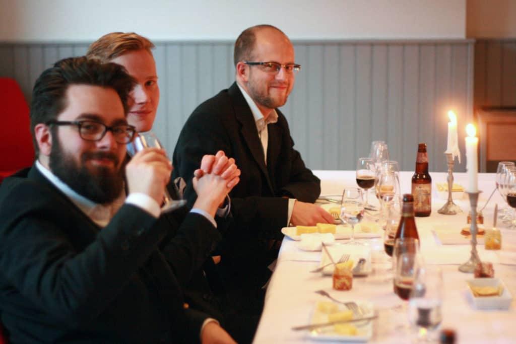 Ost och Ölprovning med tre män som sitter vid ett fint uppdukat bord och provar ost och öl