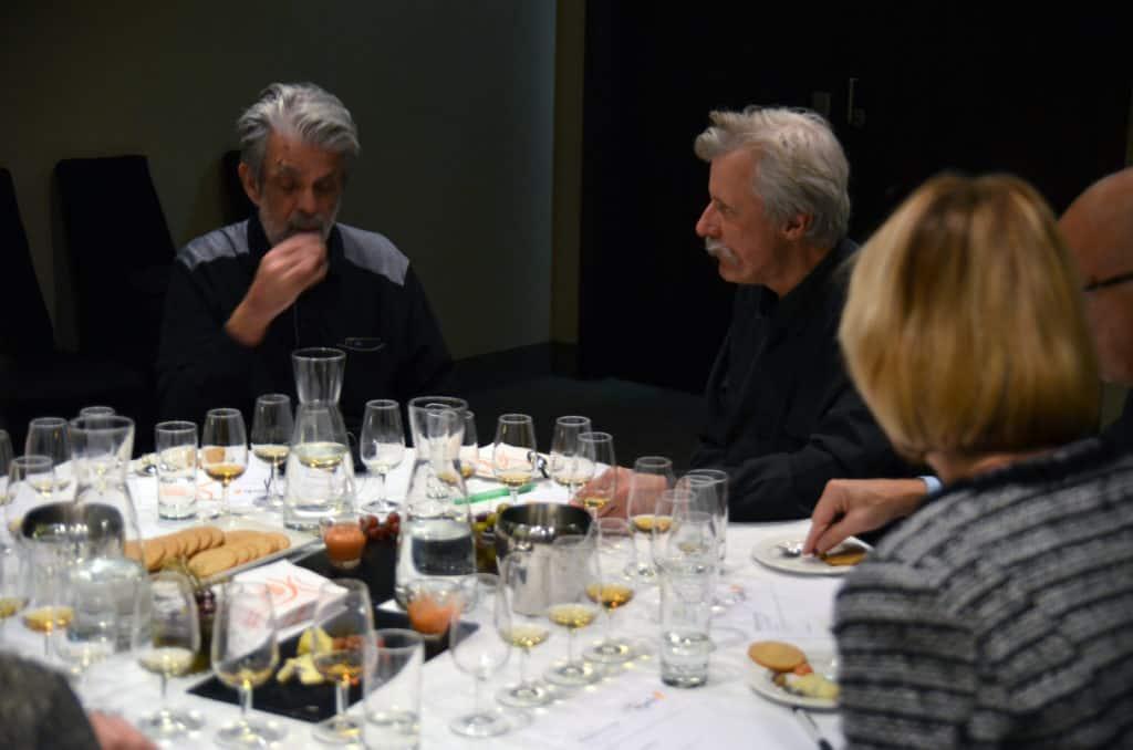 Whiskyprovning med två män som provar whisky runt ett fint uppdukat bord