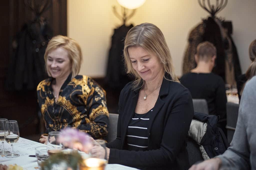 En bild på två kvinnor som besöker en upplevelse hos Taysta efter att fått den i födelsedagspresent. Borden är fint dukade med vinglas och tända ljust samt blommor