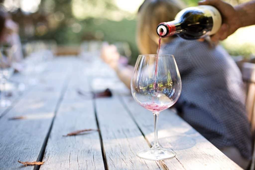 Vin hälls upp i ett vinglas på en grillfest