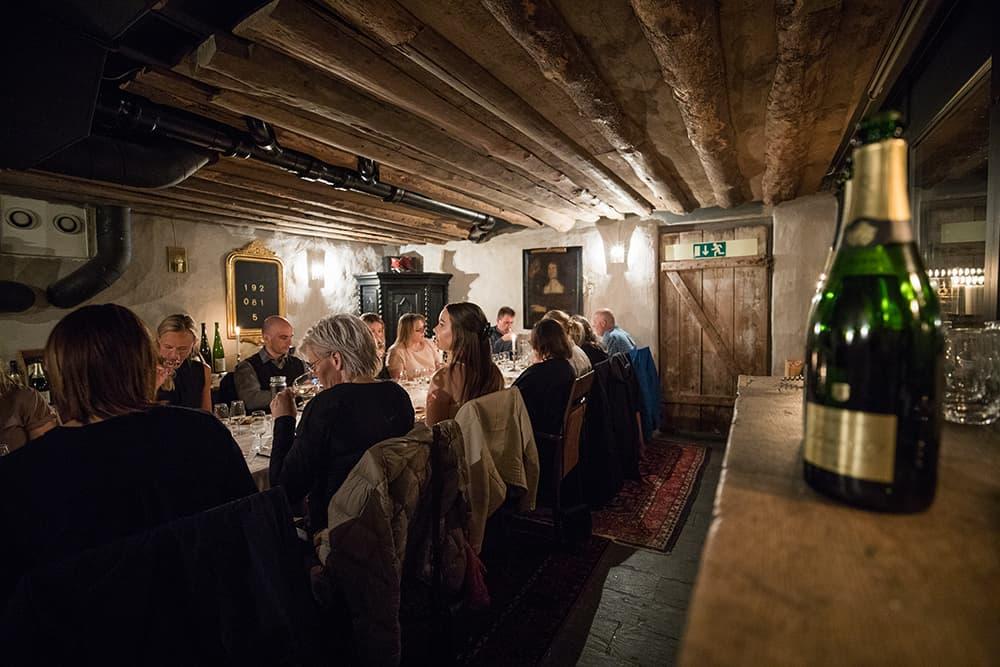 En mysig vinkällare i Örebro under en pågående vinprovning. Glada deltagare.