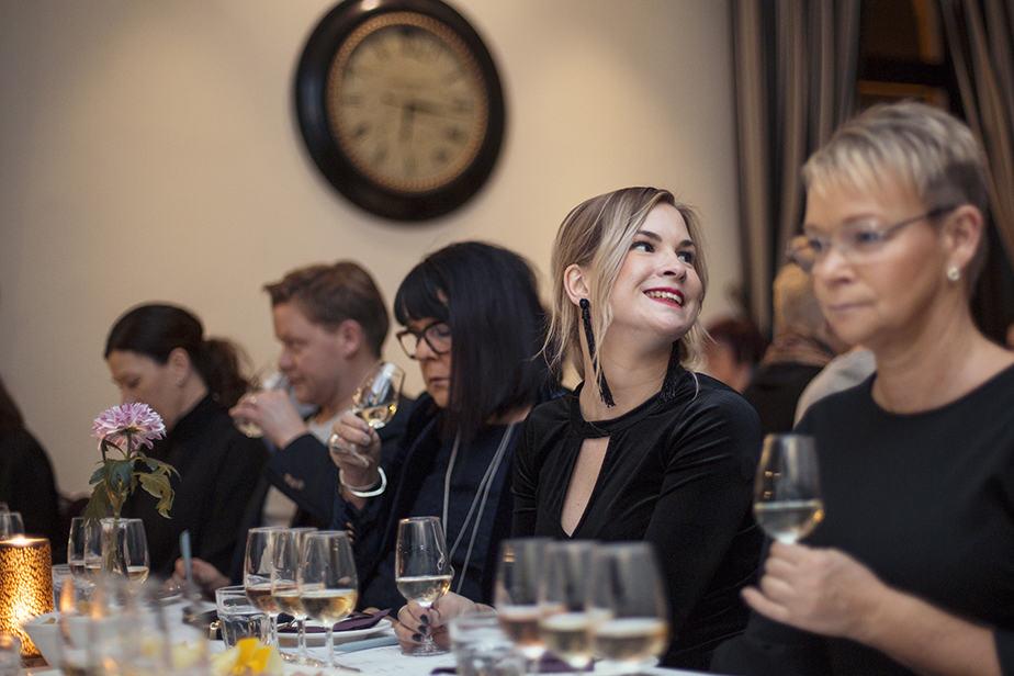 En vinprovning i Malmö med en grupp deltagare som provar och doftar på vin. Mysig stämning och tända ljus.