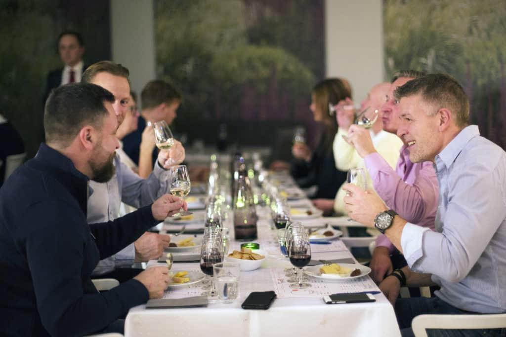 En vinprovning i Västerås med en grupp finklädda herrar som provar vin
