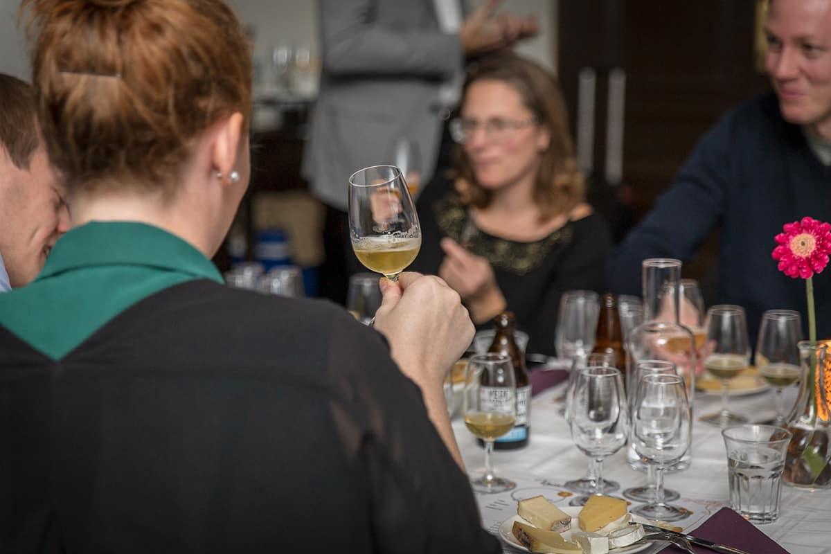 Gäster sitter runt ett fint uppdukat bord och provar öl