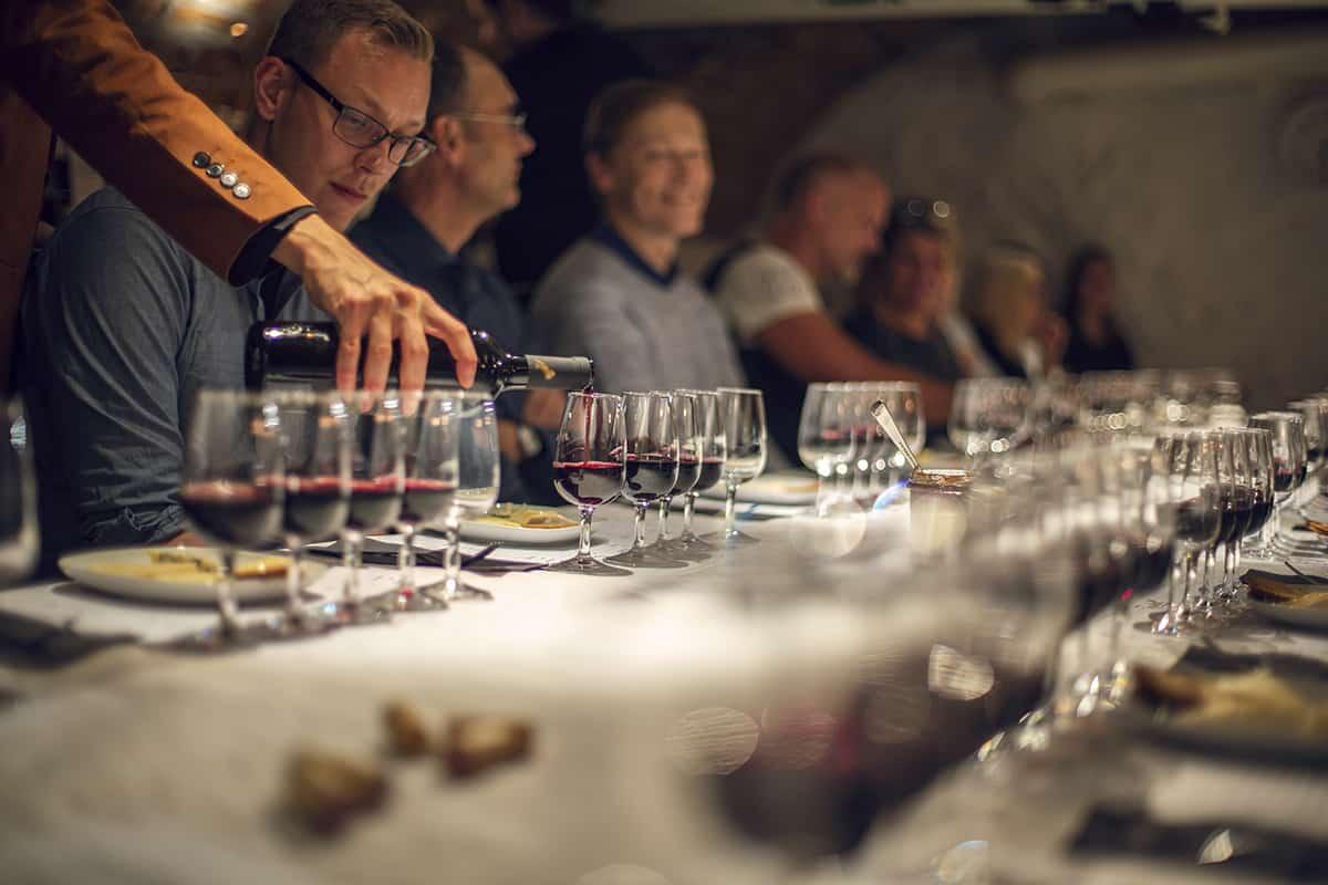 Ett uppdukat långbord med vinglas. Glada deltagare och vin fylls på.