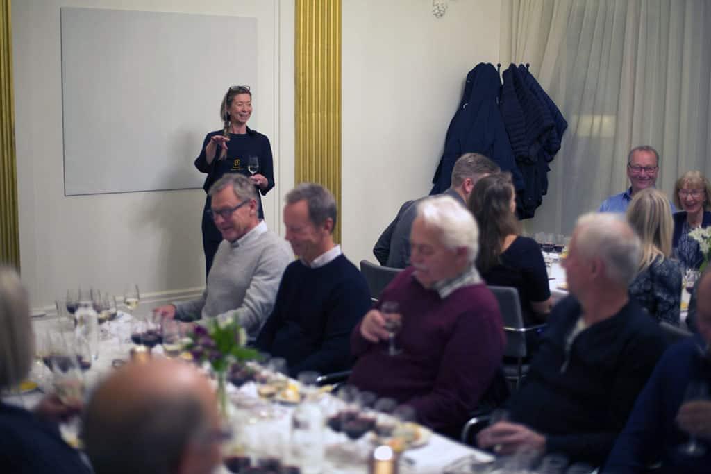 Deltagare provar vin och ost medans sommelieren talar.