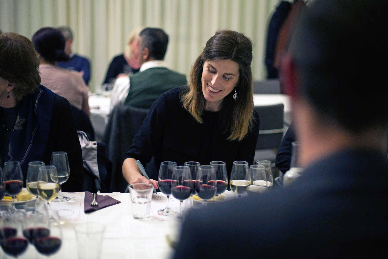 En kvinna provar olika viner och skriver ner sitt omdöme. Hon ser ut att ha roligt.