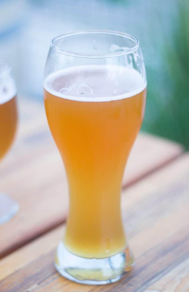 Ett ölglas med belgisk veteöl upphällt