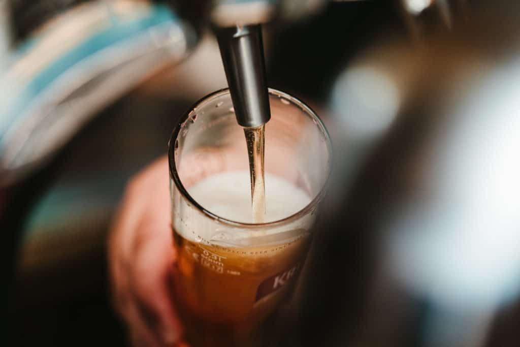 mörk öl hälls upp i ett glas från en tapp