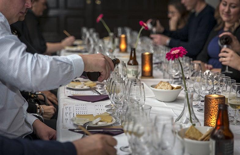 Deltagarna sitter runt ett lång bord uppdukat med ost, öl och tända ljus.