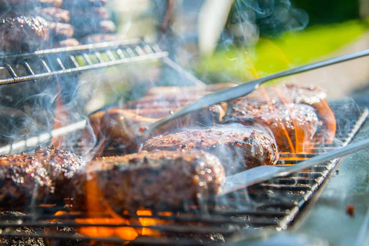 Grillad oxfile som ligger över en rykande grill med lågor